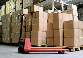 Group of carton boxes and fork pallet truck stacker in warehouse in front of cardboard boxes